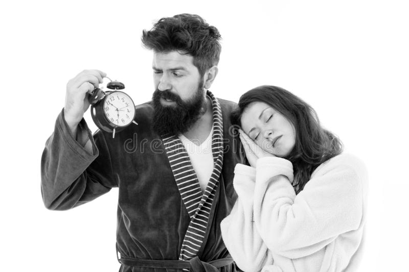 An early morning hour. Sleepy woman and bearded man holding alarm clock early in the morning. Sexy girl and brutal royalty free stock images