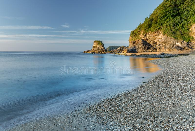 Early Morning Light, Charlestown Beach, Cornwall. Early Morning Golden Light over pebbles and cliffs, Charlestown Beach, south Cornwall stock images