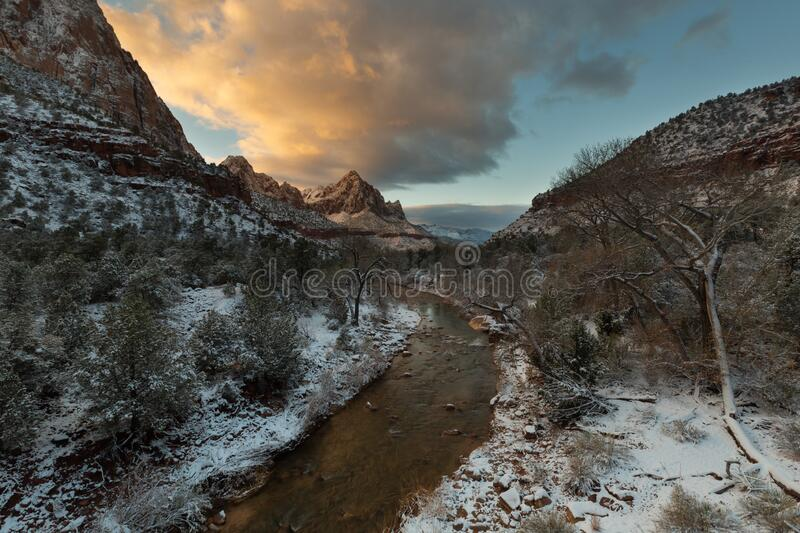Early morning view of the Virgin river in winter in Zion Nat. park. Early morning light gives a gold glow to clouds above the Virgin river and Zion national park royalty free stock images