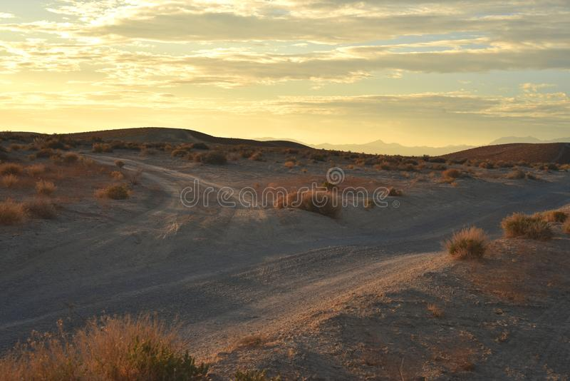 Desert dawn on dirt roads. Early morning light streaks color through the cloud filled sky over distant mountain range, closer hills, and sandy desert landscape royalty free stock photography