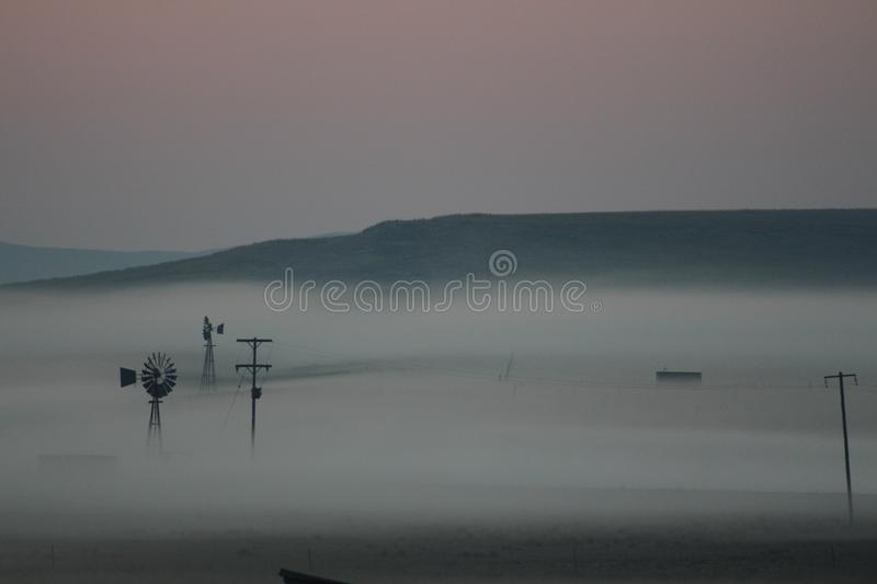 Early morning mist covering a farm and the surrounding landscape stock photos