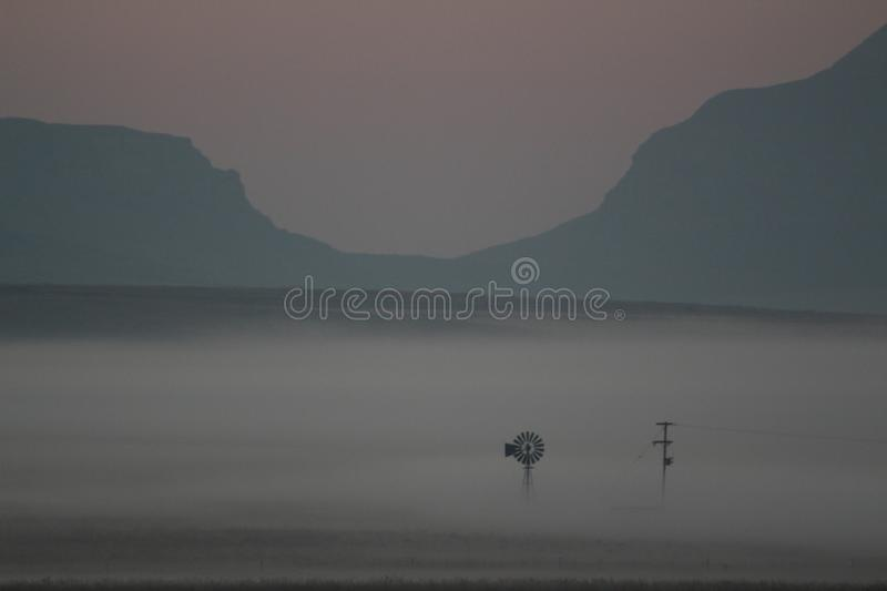 Early morning mist over a farmers field with windmills and crops barely visible royalty free stock photos