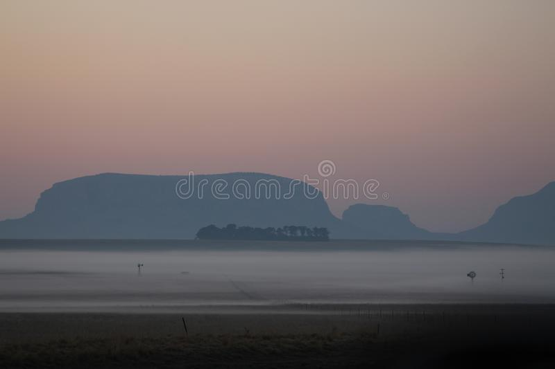 Early morning mist over a farmers field with windmills and crops barely visible stock photos