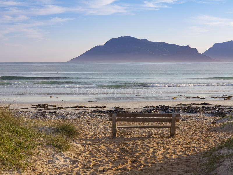 Early morning mountains, beach, and a solitary bench at Kommetjie on the Cape Peninsula in South Africa. This landscape view captures one of Kommetjie`s beaches stock images