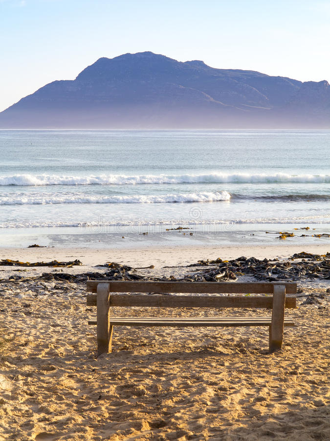 Early morning mountains, beach, and a solitary bench at Kommetjie on the Cape Peninsula in South Africa. This portrait view captures one of Kommetjie`s beaches royalty free stock photography
