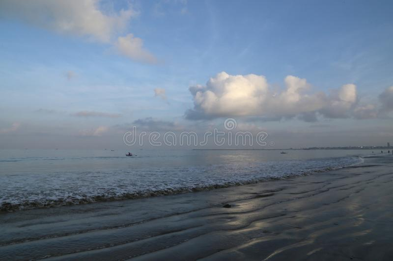 Early morning on the ocean beach, arriving from waves, clouds and wet sand stock photos