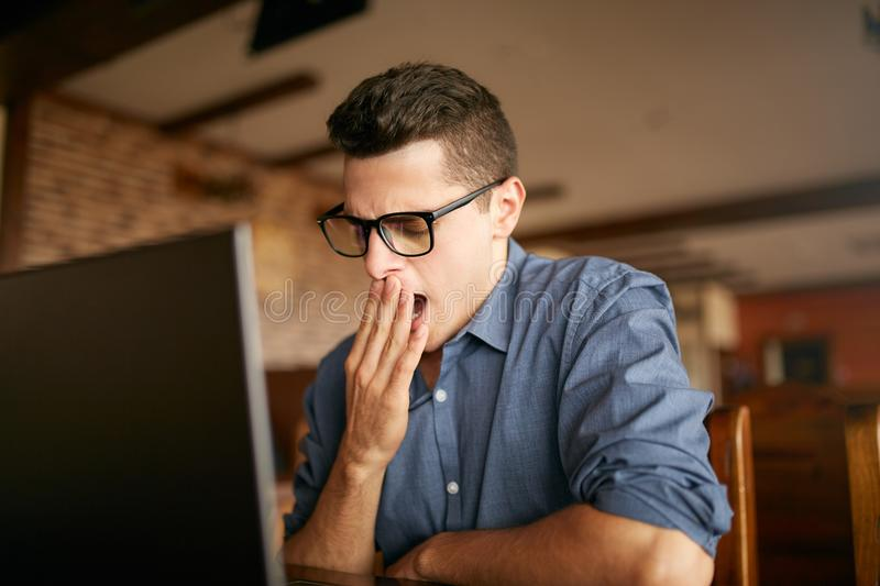 Early morning in the office. Sleepy tired handsome hipster freelancer in glasses is yawning at his work place in front royalty free stock images