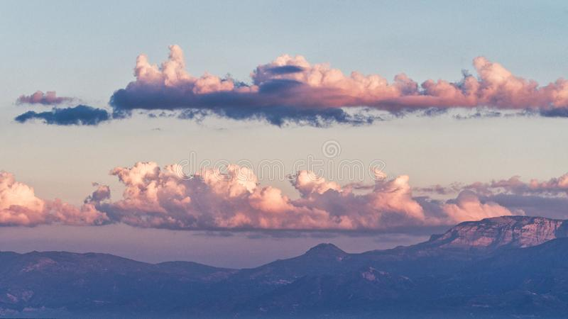 Pink Cloud Banks Over Peloponnese Mountains, Greece. Early morning pink light highlighting two distinct cloud banks over blue Peloponnese mountain ranges, Greece royalty free stock image