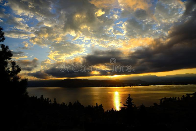 Skyscape Scenic at Sunrise along Lake Okanagan shore BC Canada. Skyscape after sunrise over lake Okanagan shore near Kelowna BC Canada in mountains with sunlight stock photo