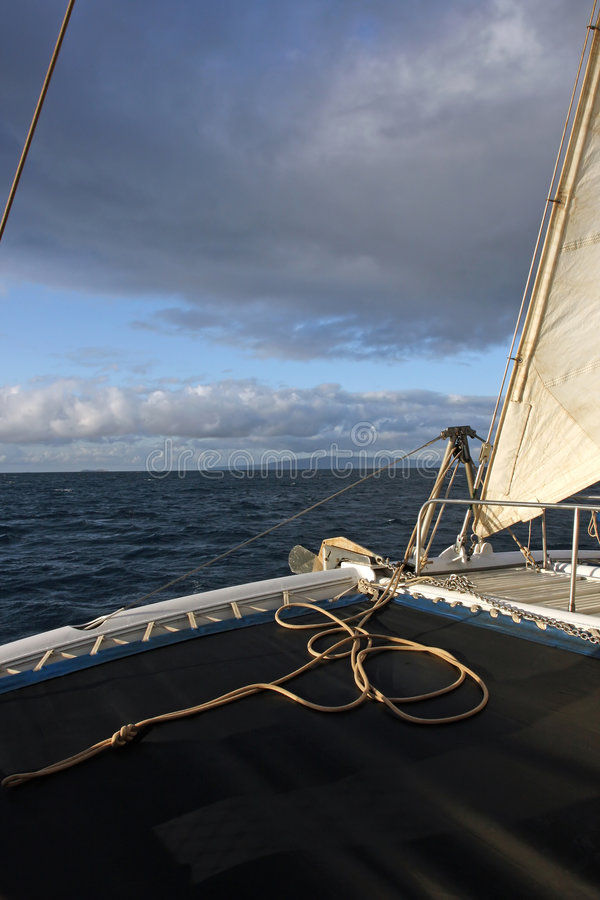 Early Morning Sail. The wind partially filling the sails on a catamaran boat with what looks like a stormy sky ahead stock photography