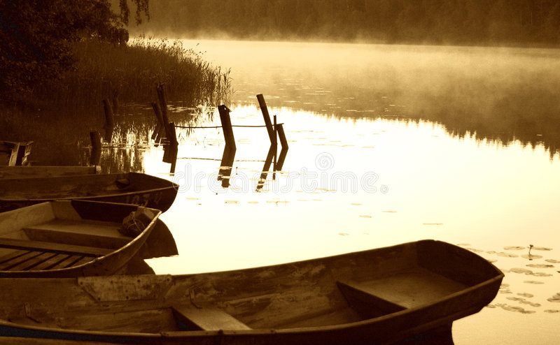 Early morning sketch by the foggy lake with boats stock image