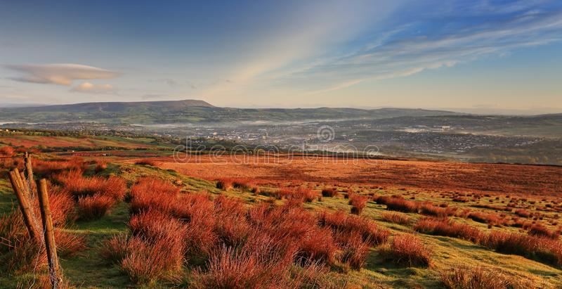 View to Pendle Hill from Crown Point, Burnley. The early morning sun casts a warm glow on the hillside above Burnley, Lancashire. Pendle Hill can be seen on the stock photography