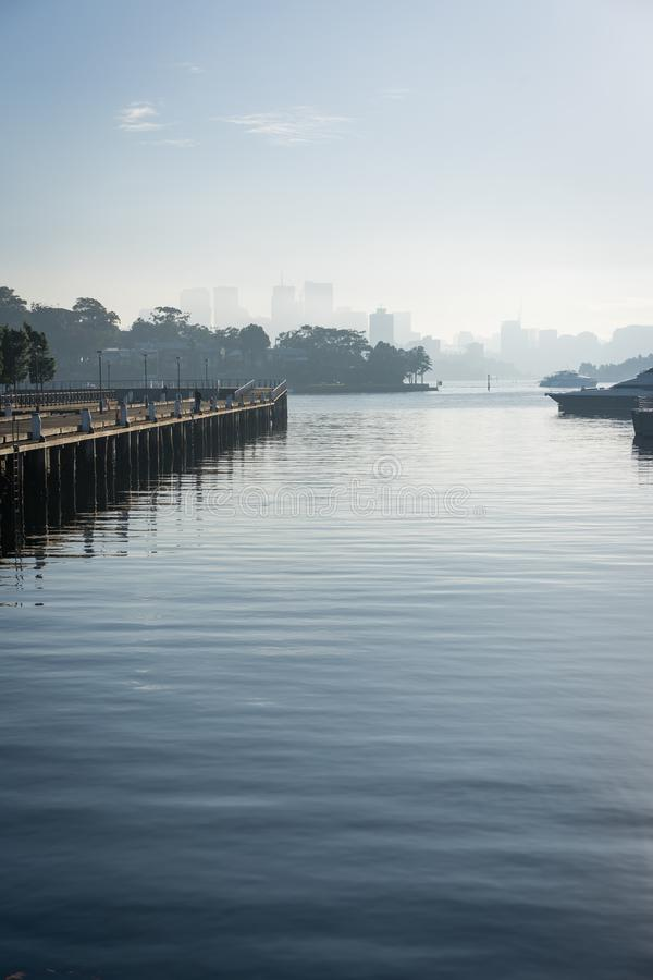 Early morning sun haze over the water at Pirrama Park/Jones Bay Wharf, Sydney NSW. June 2019. Taken from the boardwalk section of Pirrama Park. Portrait stock image