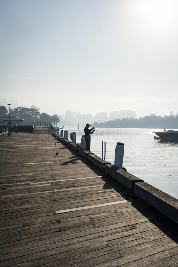 Early morning sun haze over the water at Pirrama Park/Jones Bay Wharf, Sydney NSW. June 2019. Taken from the boardwalk section of Pirrama Park. Portrait stock photography