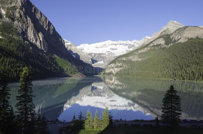 Early morning sun on Lake Louise. With a reflection like a mirror and mist on the water. Banff Alberta Canada royalty free stock photos