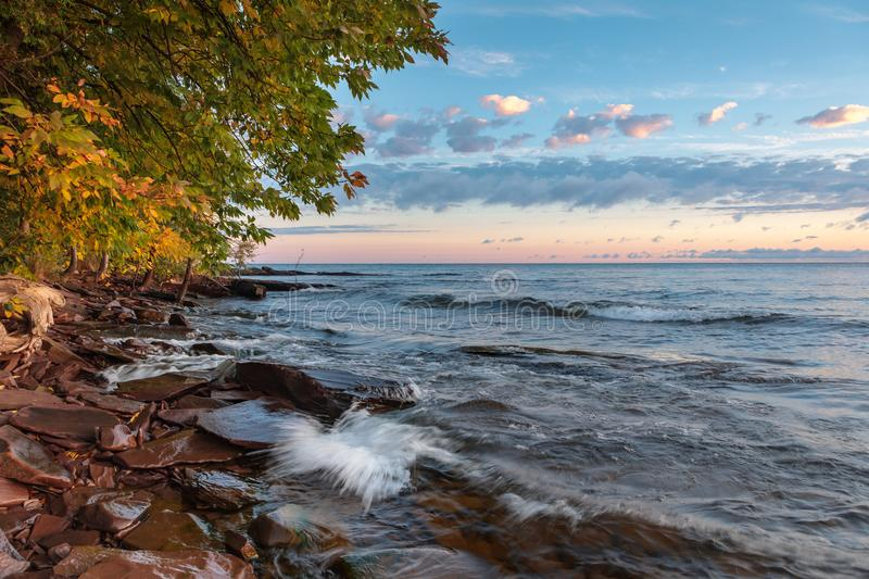 Lake Superior Rocky Shoreline in Northern Michigan, USA. Early morning sun lights up sandstone rocks and tree branches as Lake Superior waves roll up to the stock photos