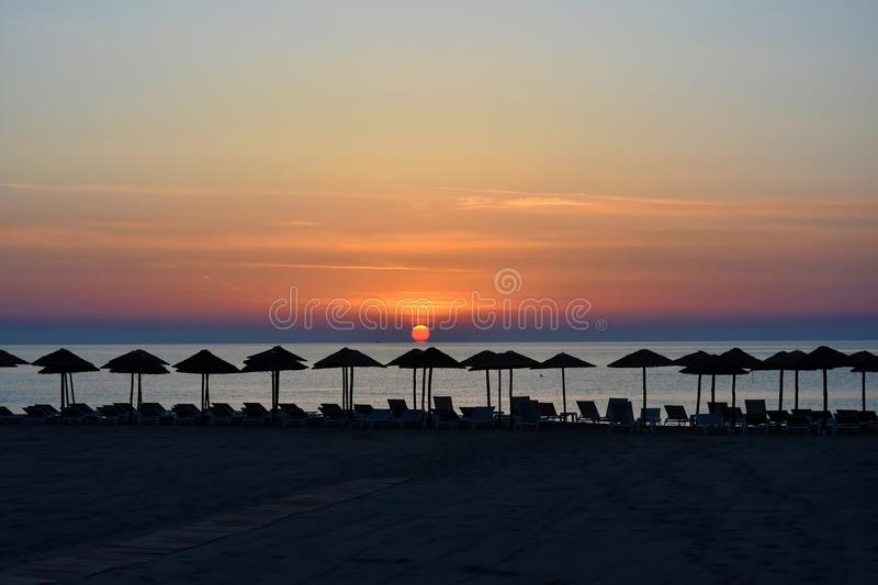 Sunrise at a beach in Katerini , greece. Early morning sunrise at a beach in Katerini, greece. In the foreground straw parasols and beach loungers royalty free stock images