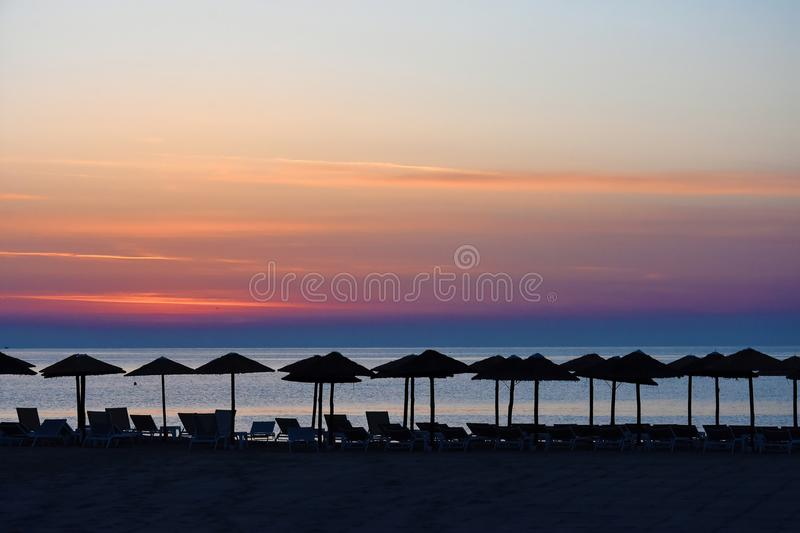Sunrise at a beach in Katerini , greece. Early morning sunrise at a beach in Katerini, greece. In the foreground straw parasols and beach loungers royalty free stock photography