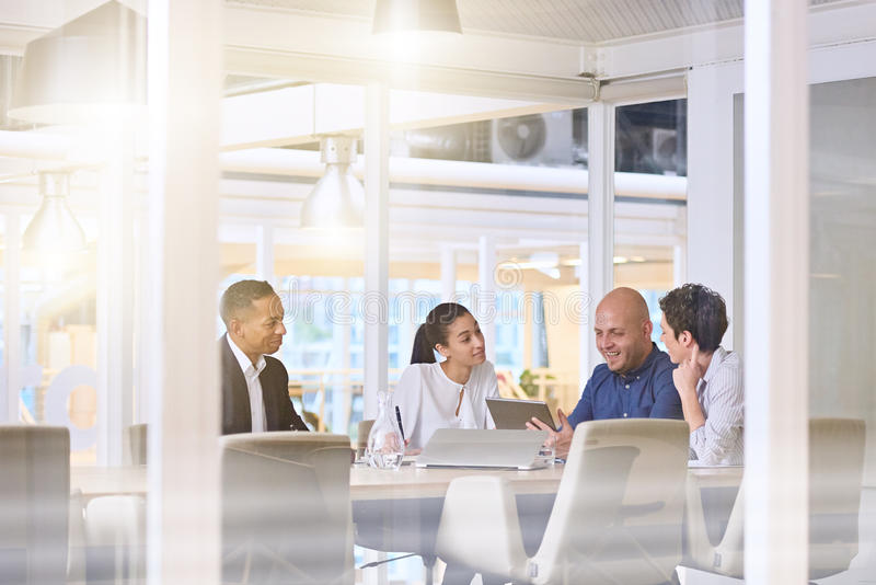Early morning sunrise business meeting in modern office conference room. Corporate business meeting in modern office with glass walls, flare from the sunlight royalty free stock photo