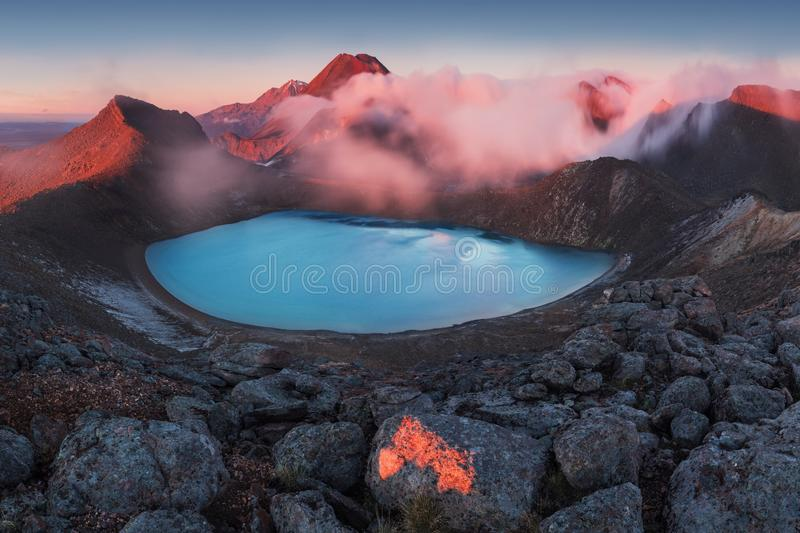 Tongariro alpine crossing. Early morning sunrise, landscape scenery of blue lake, wild mountains and huge volcano. royalty free stock photo