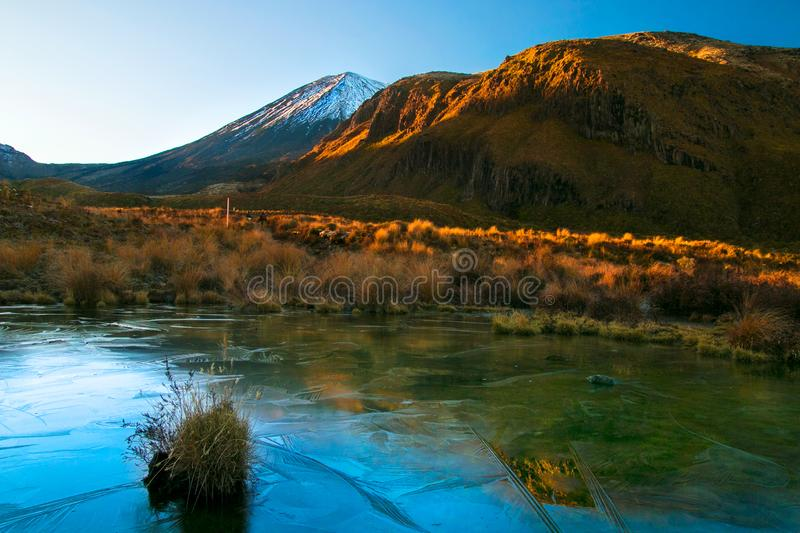 Early morning sunrise, landscape scenery of frozen blue pure water lake, wild mountains and huge volcano with snow on the peak stock photos