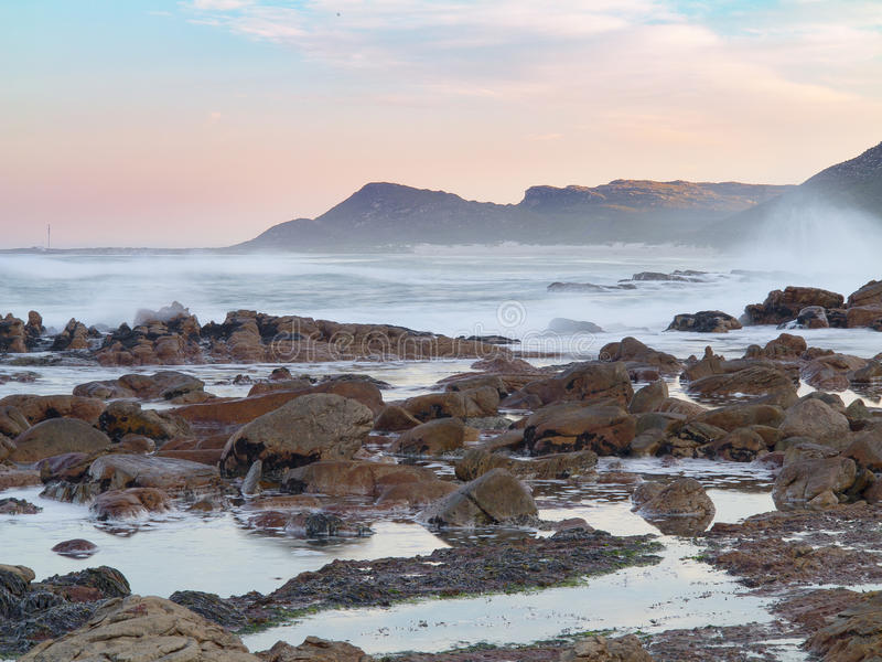 Early morning tide and surf at Scarborough on the Cape Peninsula in South Africa. This photograph catches the tidal movement as a long exposure, where the rocks royalty free stock images