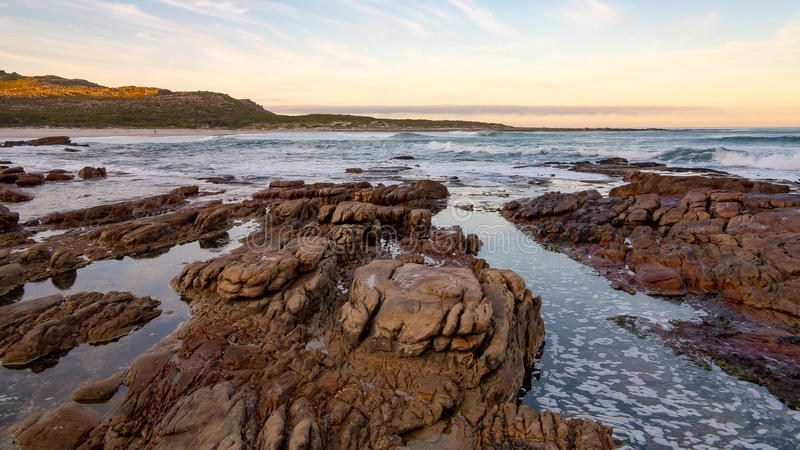 Early morning tide and surf at Scarborough on the Cape Peninsula in South Africa. This photograph is a wide-angle shot of the rocks and surf on a calm morning stock images