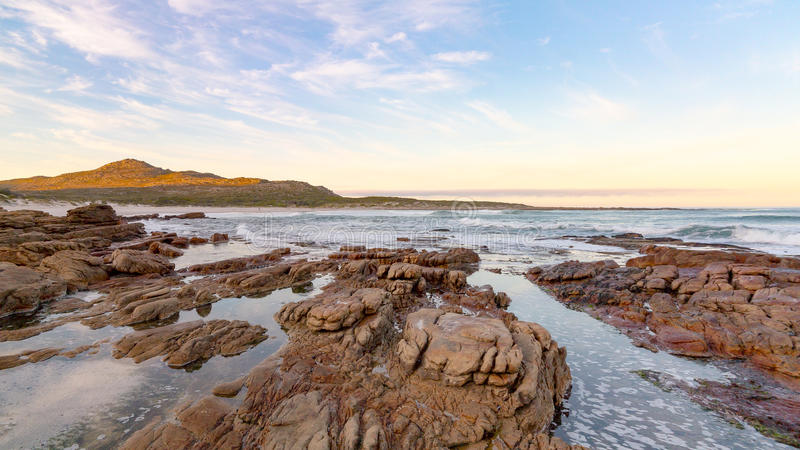 Early morning tide and surf at Scarborough on the Cape Peninsula in South Africa. This photograph is a wide-angle shot of the rocks and surf on a calm morning stock image
