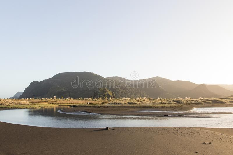 The river, mountains and black sand of Whatipu Beach, Waitakere Ranges, Auckland, New Zealand. royalty free stock image