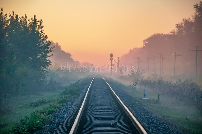 Early morning view of railway line going straight ahead through autumn fog to rising sun. Sunrise haze direction perspective lights shadow smog visibility mist stock photos