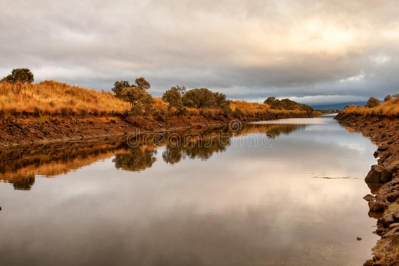 Early morning view of waterway. With sunrise clouds reflecting in the water royalty free stock photo