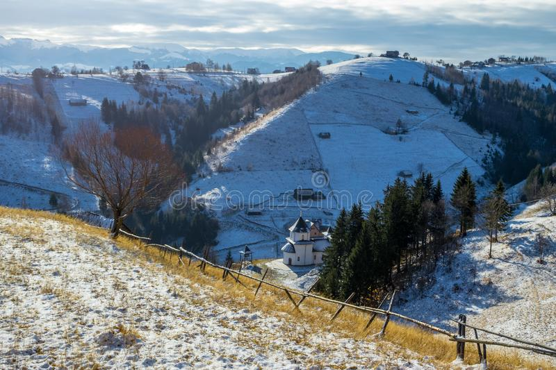 Early morning Winter panorama with a church and wooden houses on snowy hills. In the rural village Magura, Brasov, a touristic destination in Romania stock photography
