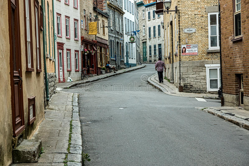 Early Mprong in Quebec City. Quebec, Canada - Spetember 11, 2015: A man walks the deserted, European style streets of Quebec City in the early, pre-dawn light stock image