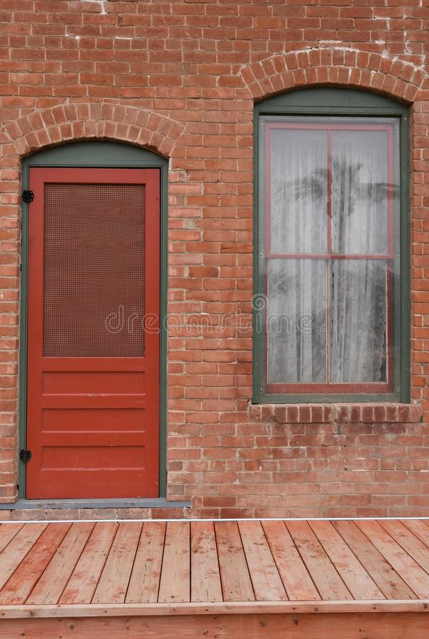 Window and red door on brick building with palm tree reflected in window royalty free stock photography