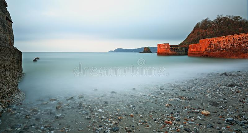 Tranquil waters lap up the beach at Charlestown, Cornwall. The early sun lights up the Charlestown harbour wall with a tint of red as the milky water laps up the royalty free stock photos