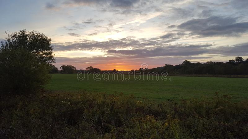 Early sunrise over green field royalty free stock images