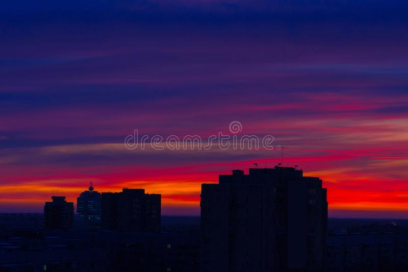 Early winter morning over the city. Red-blue bright sky. The sun has not yet risen. The city begins to wake up royalty free stock photos