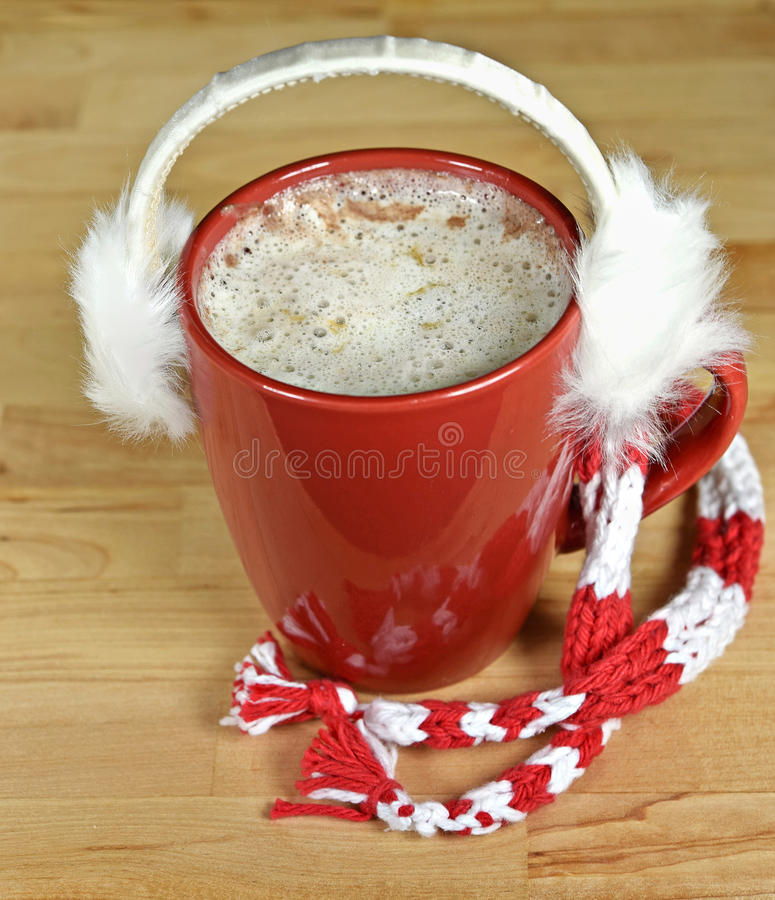 Earmuffs on hot chocolate drink stock image