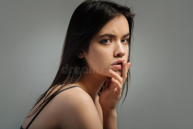 Earnest dark-haired woman touching her lips. Poser. Good-looking stern long-haired young woman staring and touching her lips and having her mouth half opened royalty free stock photos