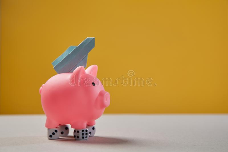 Earning, finance, investment, startup and stock market concept. Pink piggy, dice and rocket taking off.  royalty free stock photography