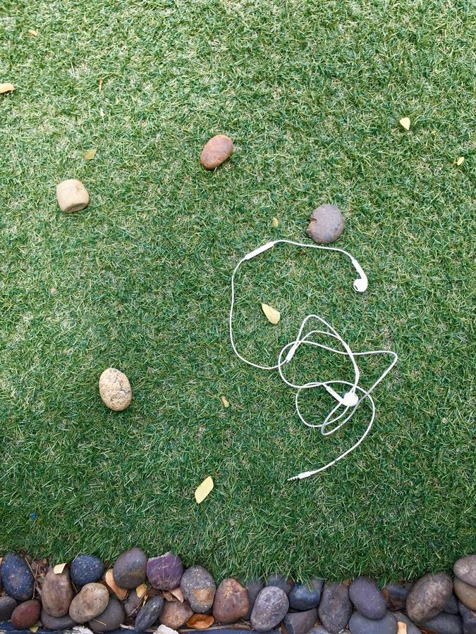 Earphone. On background of grass and stone royalty free stock photography