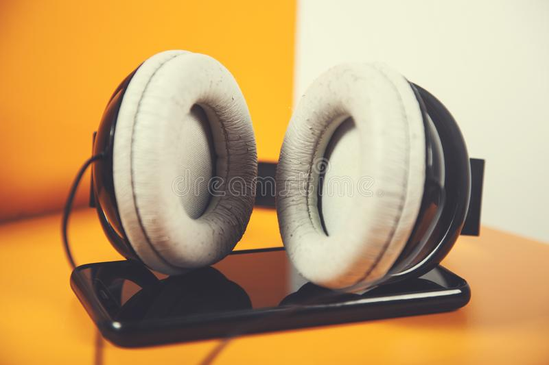 Earphone with phone. Earphone with smart phone on the orange background royalty free stock photos
