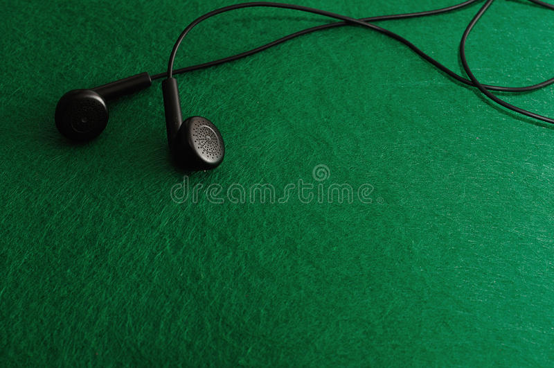 Earphones. Isolated against a green background stock images