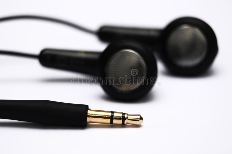 Earphones with jack. Black earphones with golden stereo jack stock photography