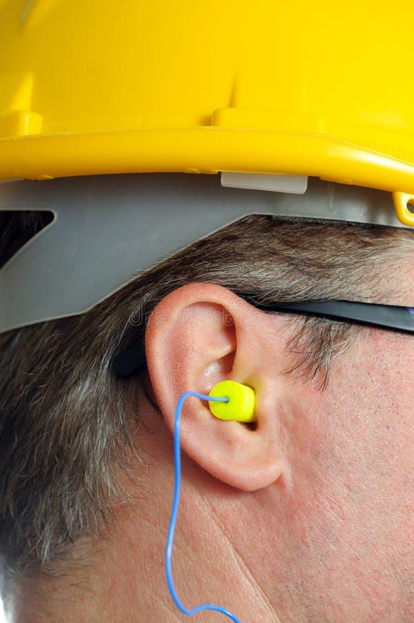 Earplug amarelo na orelha foto de stock