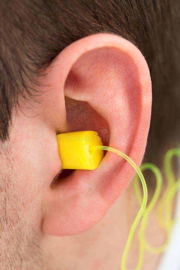 Earplug amarelo na orelha fotografia de stock royalty free
