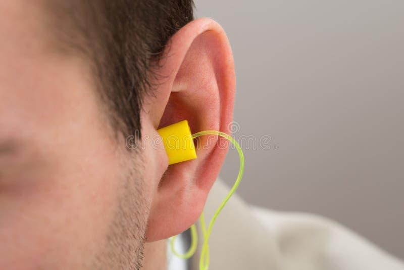 Earplug amarelo na orelha imagem de stock