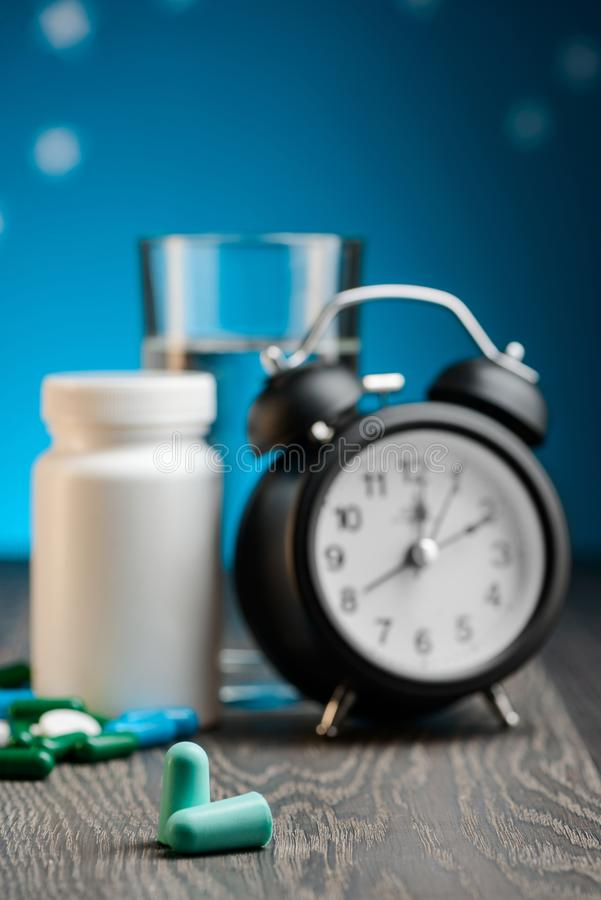 Earplugs, alarm clock and pills. On a bedside table, selective focus. Insomnia problem solution, noisy sound block stock photo
