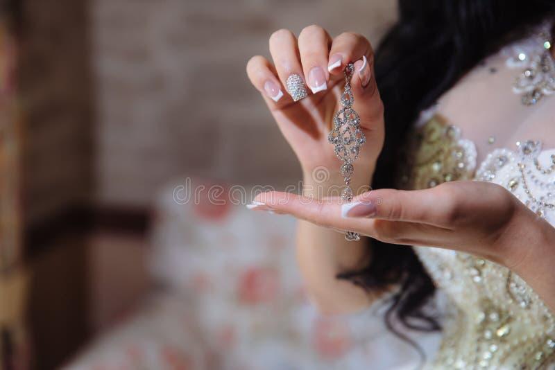 Earrind i händerna av bruden royaltyfri foto