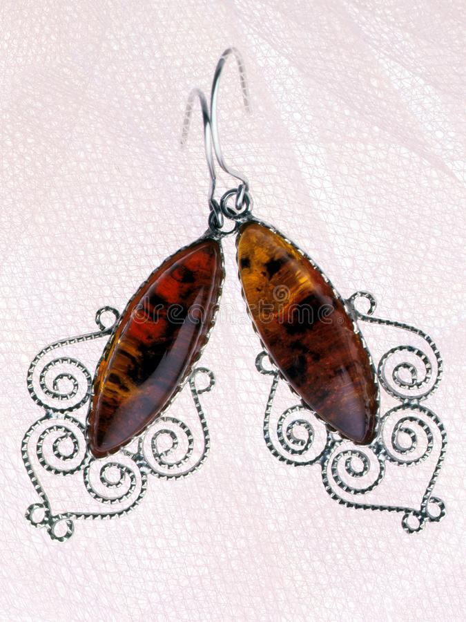 Earrings with amber. The beauty of the stone. Yellow, transparent amber. Still life. stock images